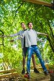 Meninos de sorriso que têm o divertimento no campo de jogos Crianças que jogam fora no verão Adolescentes que montam em um balanç Imagem de Stock Royalty Free