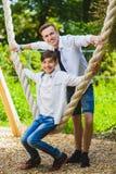 Meninos de sorriso que têm o divertimento no campo de jogos Crianças que jogam fora no verão Adolescentes que montam em um balanç Foto de Stock Royalty Free