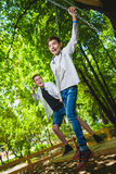 Meninos de sorriso que têm o divertimento no campo de jogos Crianças que jogam fora no verão Adolescentes que montam em um balanç Fotos de Stock
