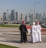 Meninos do Oriente Médio árabes na estrada transversaa que olha na opinião da skyline de Doha Catar, Médio Oriente imagem de stock