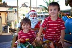 Meninos doces, irmãos, montando em um pequeno trenó de Santa Claus em um alegre Foto de Stock Royalty Free