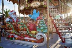 Meninos doces, irmãos, montando em um pequeno trenó de Santa Claus em um alegre Fotos de Stock