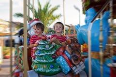 Meninos doces, irmãos, montando em um pequeno trenó de Santa Claus em um alegre Fotografia de Stock Royalty Free