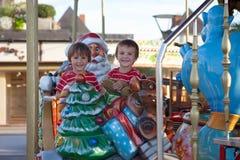 Meninos doces, irmãos, montando em um pequeno trenó de Santa Claus em um alegre Imagens de Stock Royalty Free