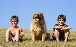 Meninos e cão em um monte Imagens de Stock