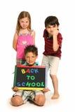 Meninos e menina irritados com de volta a sinal da escola fotografia de stock royalty free