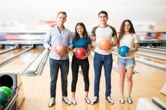 Meninos e meninas com as bolas de boliches coloridas que estão no clube Fotos de Stock