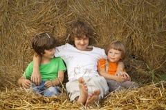 3 meninos em um monte de feno no campo Fotos de Stock Royalty Free