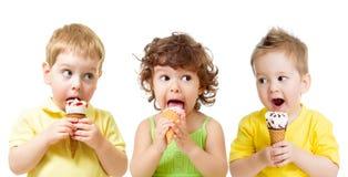 Meninos engraçados e menina das crianças que comem o cone de gelado isolado Fotografia de Stock