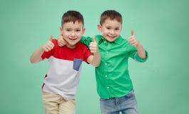 Meninos felizes que mostram os polegares acima sobre a administração da escola Fotografia de Stock