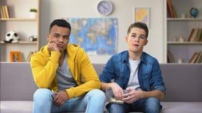 Meninos multirraciais furados que olham a tevê comer petiscos, conexão velha lenta da tecnologia video estoque