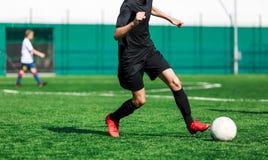 Meninos na corrida preta do sportswear, fluxo, ataque no campo de futebol r Treinamento imagem de stock royalty free
