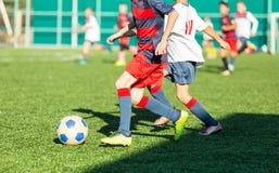 Meninos no sportswear azul vermelho que corre no campo de futebol Os jogadores de futebol novos pingam e retrocedem a bola do fut foto de stock royalty free