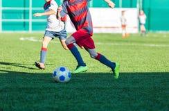 Meninos no sportswear azul vermelho que corre no campo de futebol Os jogadores de futebol novos pingam e retrocedem a bola do fut foto de stock