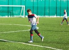 Meninos no sportswear branco vermelho que corre no campo de futebol Os jogadores de futebol novos pingam e retrocedem a bola do f foto de stock