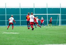 Meninos no sportswear branco vermelho que corre no campo de futebol Os jogadores de futebol novos pingam e retrocedem a bola do f imagens de stock