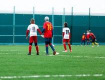 Meninos no sportswear branco vermelho que corre no campo de futebol Os jogadores de futebol novos pingam e retrocedem a bola do f fotos de stock royalty free