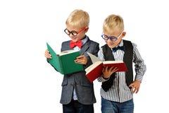 Meninos novos de sorriso dos amigos nos vidros e nos livros de leitura do bowtie Conceito educacional Isolado sobre o branco fotografia de stock