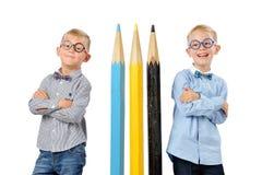 Meninos novos engraçados do retrato nos vidros e bowtie que levanta perto dos lápis coloridos enormes Conceito educacional Isolad imagem de stock