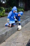 Meninos novos que jogam com o barco do brinquedo na chuva 1 Imagens de Stock Royalty Free