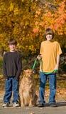 Meninos que andam o cão imagens de stock