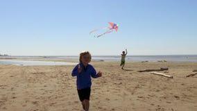 Meninos que correm com os papagaios na praia video estoque