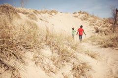 Meninos que exploram uma duna de areia Imagens de Stock