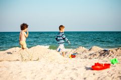 Meninos que jogam com a areia na praia imagens de stock