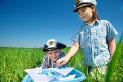 Meninos que jogam com barcos de papel Fotografia de Stock Royalty Free