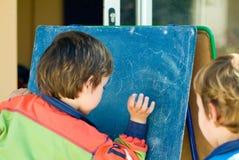 Meninos que jogam com quadro-negro Fotografia de Stock