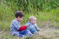 Meninos que jogam junto na grama no país imagem de stock royalty free