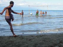 Meninos que jogam o futebol na costa de Livingston Foto de Stock