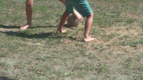 Meninos que jogam o futebol na grama