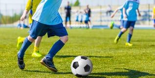 Meninos que jogam o jogo de fósforo do futebol do futebol Foto de Stock