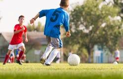 Meninos que jogam o jogo de futebol do futebol no campo de esportes Foto de Stock