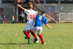 Meninos que jogam o jogo de futebol do futebol no campo de esportes Fotos de Stock Royalty Free
