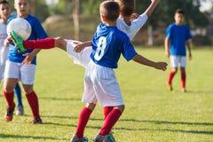 Meninos que jogam o jogo de futebol do futebol no campo de esportes Fotografia de Stock