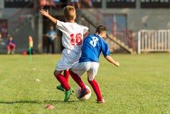 Meninos que jogam o jogo de futebol do futebol no campo de esportes Imagens de Stock