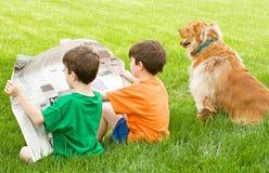 Meninos que lêem o jornal fotos de stock