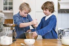 Meninos que misturam a massa em uma bacia usando um batedor de ovos Imagens de Stock Royalty Free