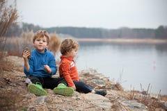Meninos que olham o lago com rochas Imagens de Stock