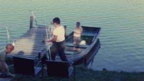 Meninos que pescam das docas do barco video estoque