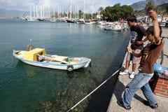 Meninos que pescam no porto de Fethiye, Turquia Foto de Stock Royalty Free