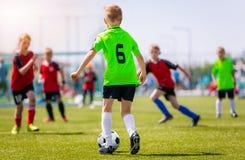 Meninos que retrocedem o fósforo de futebol na grama Jogo de futebol da juventude Competição do futebol das crianças Fotos de Stock Royalty Free