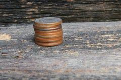 Mennicze pieniądze sterty na drewnianym podłogowym tle zdjęcia royalty free