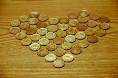 Menniczy pieniądze umieszczający na drewnianym stole jest sercowaty, miłość Wartościowościowa obrazy stock