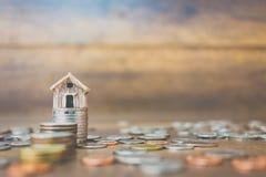 Menniczy pieniądze i dom modelujemy na drewnianym tle Zdjęcia Stock
