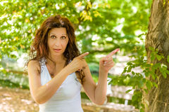Menopausal woman points with index fingers on left Stock Photo