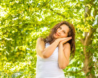 Menopausal woman rests on folded hands. Menopausal woman standing in a park rests on folded hands leaning against her cheeks as if she were sleeping Stock Photo