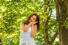 Menopausal woman rests on folded hands. Menopausal woman standing in a park rests on folded hands leaning against her cheeks as if she were sleeping Stock Photos